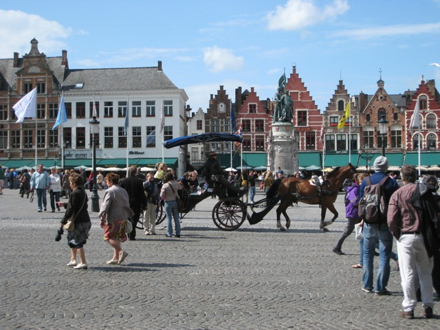"""Square in Bruges with carriages and tourists"""