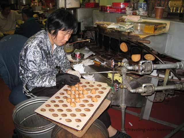 """Woman making cookies at Golden Gate Fortune Cookie Factory in Chinatown San Francisco"""