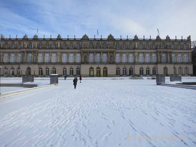 """King Ludwig's Castle seen from the front -- the grounds covered in snow"""