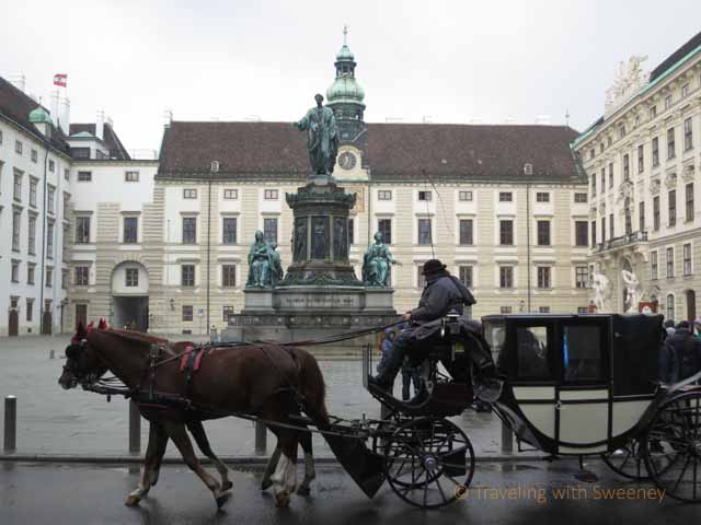 """Horse-drawn carriage in front of the Hofburg in romantic Vienna, Austria"""