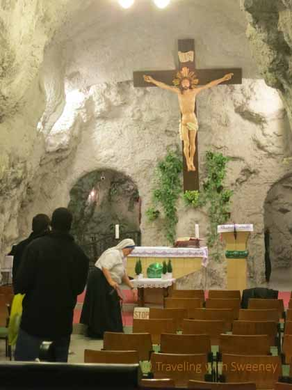 """A nun prepares the altar while visitors tour Cave Church inside the Buda's Gellert Hill"""