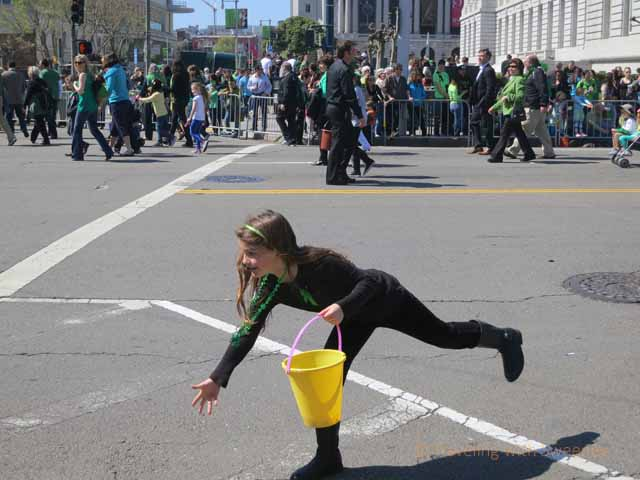 """Well-balanced young girl tossing candy into the crowd along route of St. Patrick's Day parade in San Francisco 2013"""