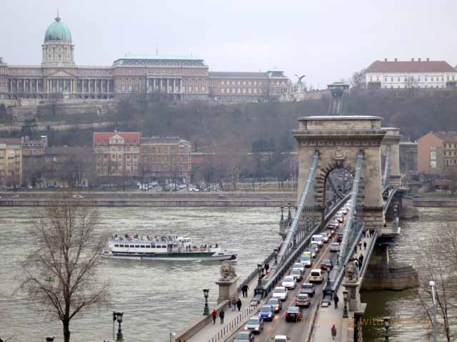 """Tour boat on the Danube River going under Széchenyi Chain Bridge, Budapest"""