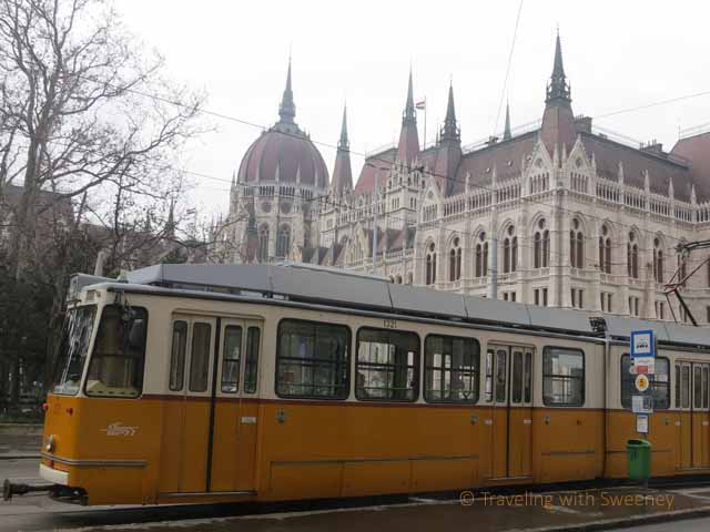 """Yellow and white tram with Budapest Parliament building in the background"""