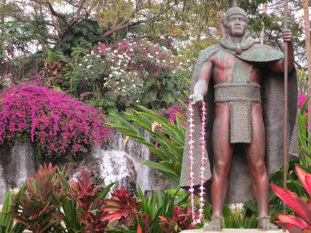"""King Kamehameha statue and beautiful flowers and waterfall at the entrance of Grand Wailea Resort, Maui"""