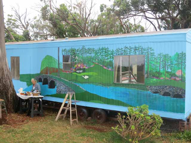 """Artist at work painting on the side of trailer at the golf course on Molokai"""