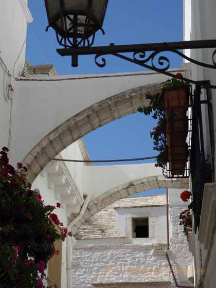 """Arches across the narrow street adorned by flowers in Locorotondo"""