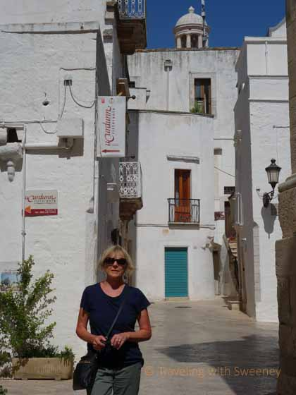 """Traveling with Sweeney walking among the whitewashed buildings of Locorotondo, Italy"""
