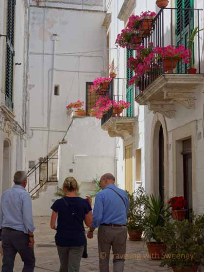 """Walking along narrow alley between whitewashed buildings with flowers in Locorotondo"""