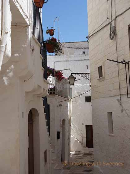 """Flower boxes mark a colorful contrast to the white buildings of Cisternino"""