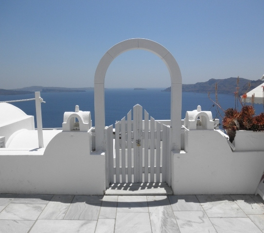 """Gate opening onto to the sea in picture perfect Oia, Santorini"""