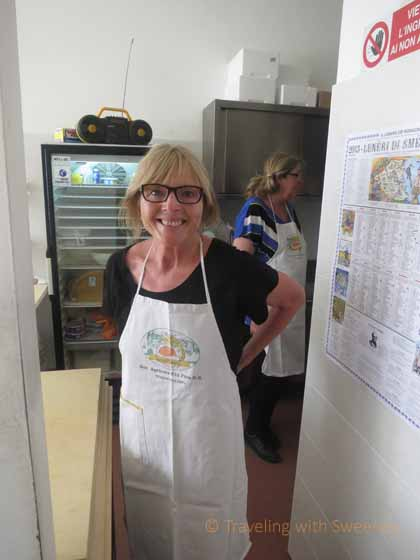 """Donning an apron before pasta making at Pasta Fresca Laura in Santarcangelo, Italy"""