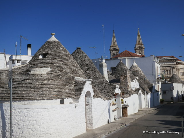 """Rione Aia Piccola area of Alberobello, Italy with the cathedral towers at the top of the hill"""