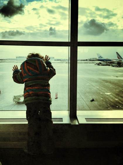 """Ready for first flight to Ireland -- Toddler looking out the airport window at planes"""