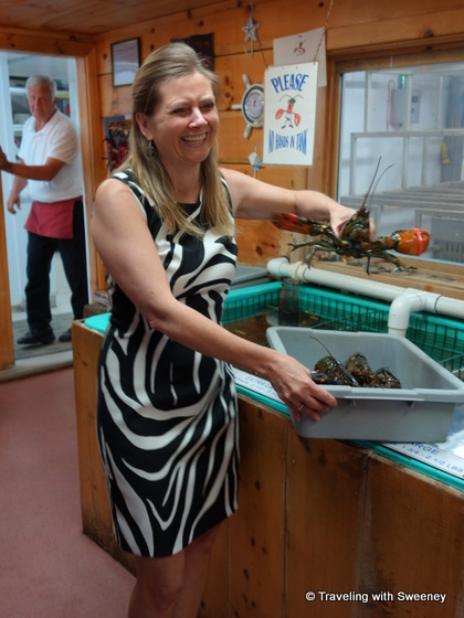 """Sharla Cameron of Hall's Harbour Lobster Pound grabbing a lobster from the tank to prepare for lunch"""