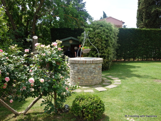 """Roses in bloom on the grounds of Casa Egle; the wishing well; and """"Green House"""" in the background where bikes for guests are stored"""