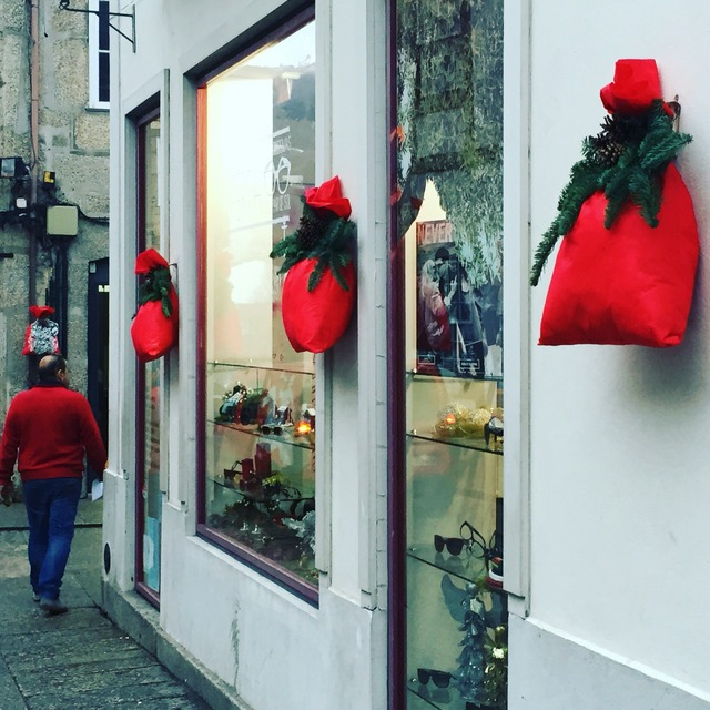Decorative red sacks and evergreen bows adorn buildings for Christmas