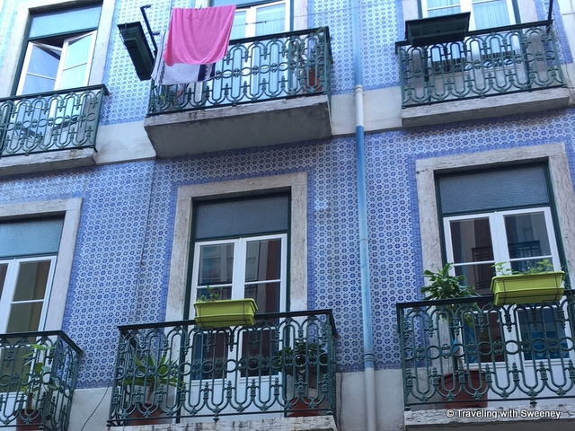 Blue tile facade of a residential building with pops of colorful flower boxes and other adornments