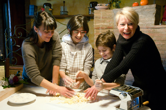 A family enjoys making pasta with Monica at La Novellina, a luxury rental villa in Tuscany