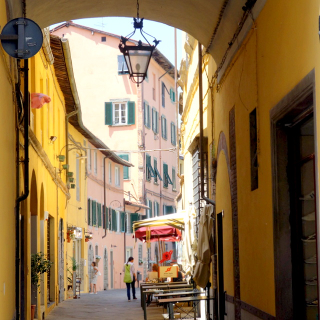 Through a passageway in Lucca, yellow and pink buildings along a narrow street in Lucca