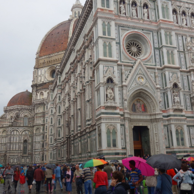 Tourists with colorful umbrella around Florence Cathedral