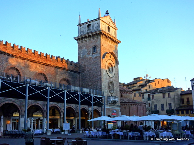 Clock tower and restaurants of Piazza dell Erbe in Manuta, Italy